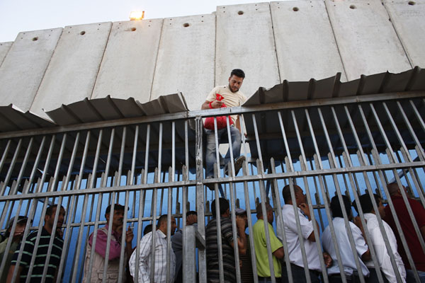 Palestinians wait to cross into Jerusalem at an Israeli checkpoint in Bethlehem
